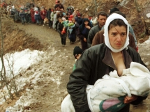 An ethnic Albanian woman feeds her baby as she and another 2,000 refugees flee Kosovo on March 30, 1999. Source: NATO.