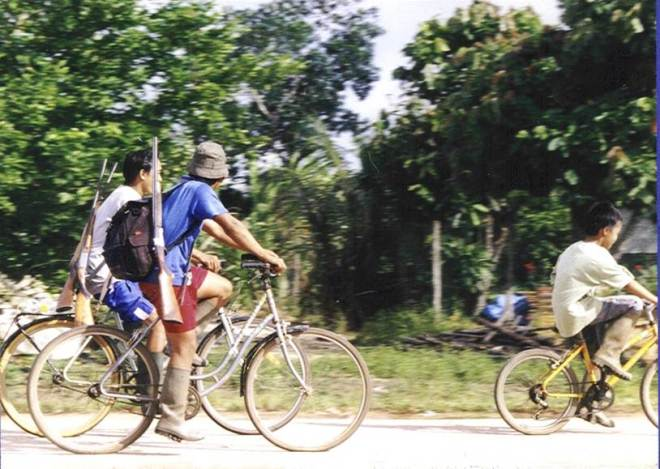Hmong men in French Guiana going hunting by bike.