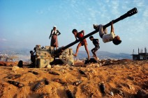 Children play on an anti-aircraft gun near Beirut, Lebanon. Steve M. Curry
