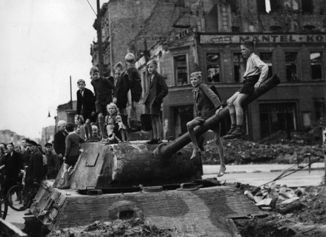 Children play on the bomb sites and wrecked tanks in Berlin, in the aftermath of the fighting in the city in 1945. Fred Ramage / Getty Images.