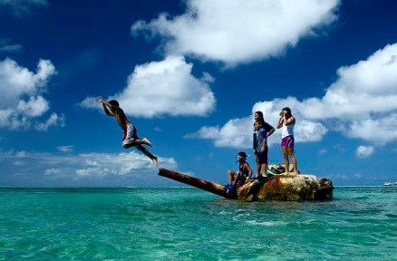 Children playing on an abandoned tank from WW2 in Saipan. Michael John Grist.