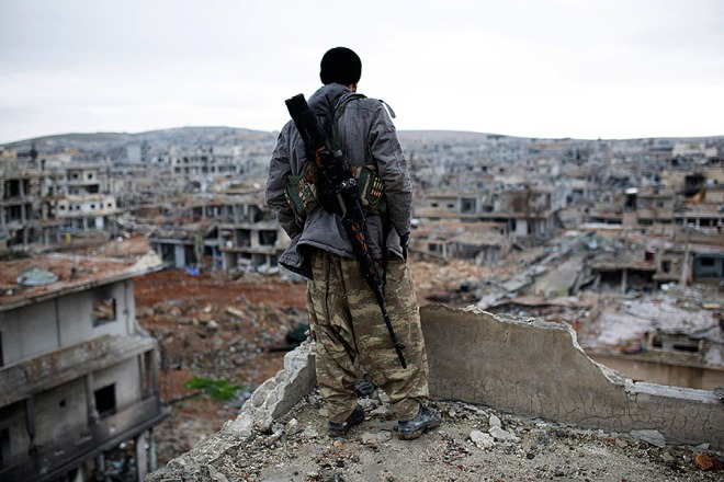 A Syrian Kurdish sniper looks at the rubble in the Syrian city of Kobane, Jan. 30, 2015.  Source: CS Monitor.